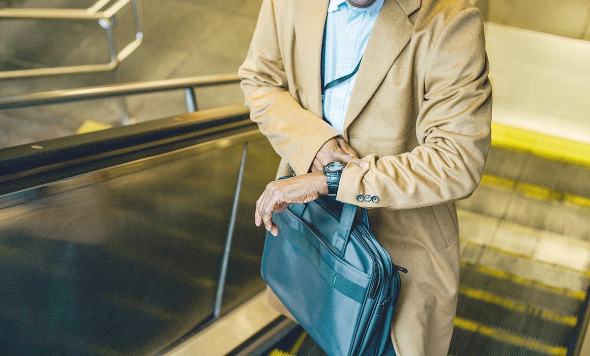 コートの男性、通勤中、時計をみる、エスカレーター